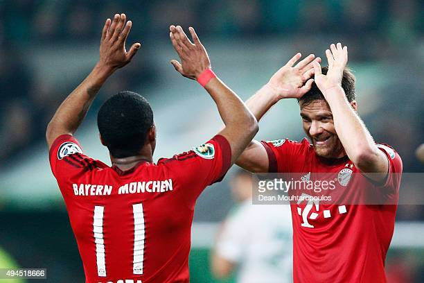 Douglas Costa and Xabi Alonso celebrate after teammate Thomas Muller of Bayern Muenchen scores his teams third goal of the game during the DFB Cup...