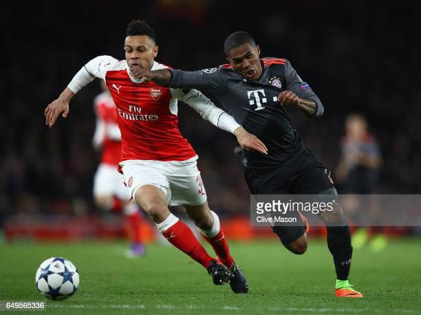 Douglas Costa of Bayern Muenchen and Francis Coquelin of Arsenal battle for the ball during the UEFA Champions League Round of 16 second leg match...