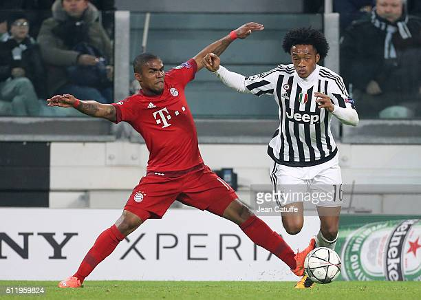 Douglas Costa of Bayern Muenchen and Juan Cuadrado of Juventus in action during the UEFA Champions League Round of 16 first leg match between...