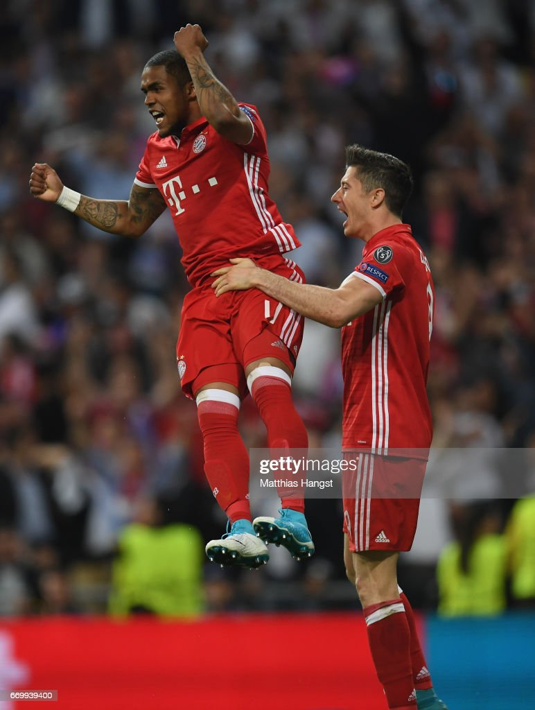 Douglas Costa of Bayern Muenchen and Robert Lewandowski of Bayern Muenchen celebrate together after Sergio Ramos of Real Madrid (not pictured) scored a own goal for Bayern Muenchen's second goal of the game during the UEFA Champions League Quarter Final second leg match between Real Madrid CF and FC Bayern Muenchen at Estadio Santiago Bernabeu on April 18, 2017 in Madrid, Spain.