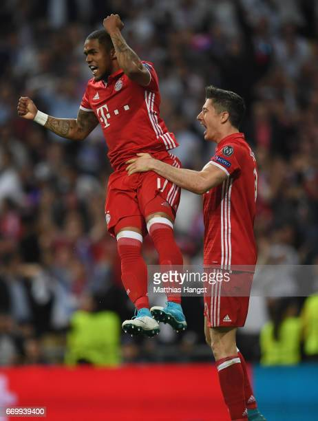 Douglas Costa of Bayern Muenchen and Robert Lewandowski of Bayern Muenchen celebrate together after Sergio Ramos of Real Madrid scored a own goal for...