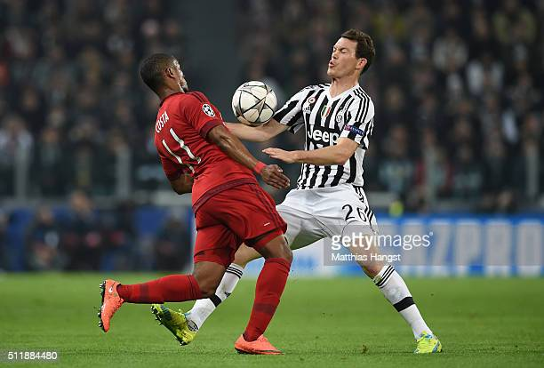 Douglas Costa of Bayern Muenchen and Stephan Lichsteiner of Juventus compete for the ball during the UEFA Champions League round of 16 first leg...