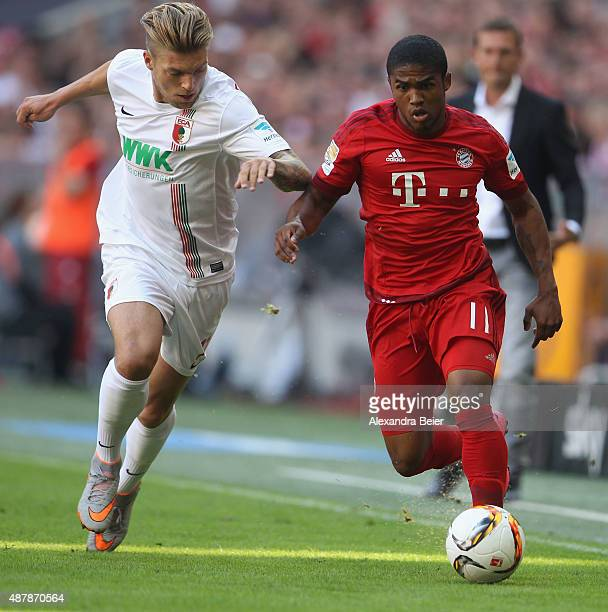 Douglas Costa of Bayern Muenchen fights for the ball with Alexander Esswein of FC Augsburg during the Bundesliga match between FC Bayern Muenchen and...