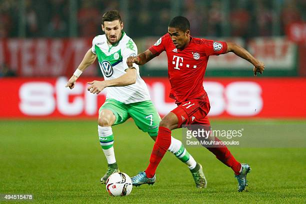 Douglas Costa of Bayern Muenchen gets past the trackle from Daniel Caligiuri of VfL Wolfsburg during the DFB Cup match between VfL Wolfsburg and FC...
