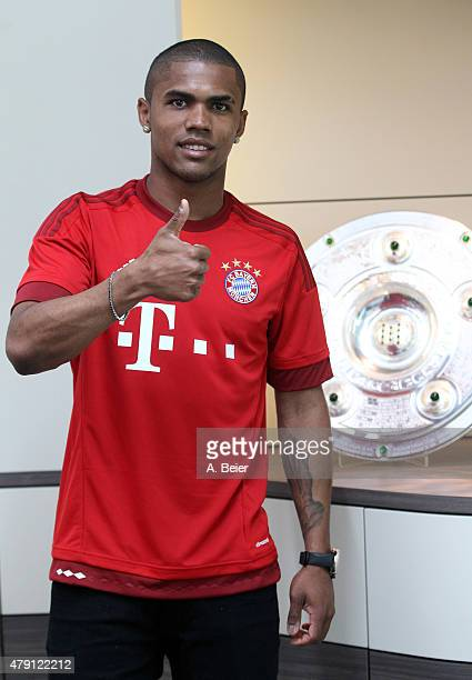 Douglas Costa of Bayern Muenchen gives a thumb up after he signed his new contract at the FC Bayern Muenchen training ground at Saebener Strasse on...