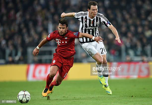Douglas Costa of Bayern Muenchen holds off the challenge from Stephan Lichsteiner of Juventus during the UEFA Champions League round of 16 first leg...