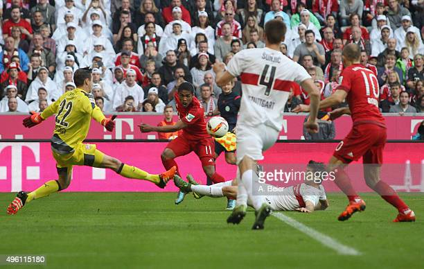 Douglas Costa of Bayern Muenchen plays the ball to Arjen Robben to score his first goal against goalkeeper Przemyslaw Tyton of VfB Stuttgart during...