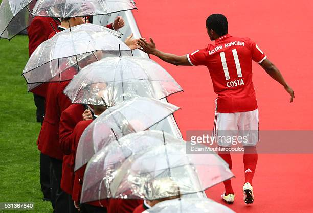 Douglas Costa of Bayern Muenchen shakes hands with club legends during the Bundesliga match between FC Bayern Muenchen and Hannover 96 at Allianz...