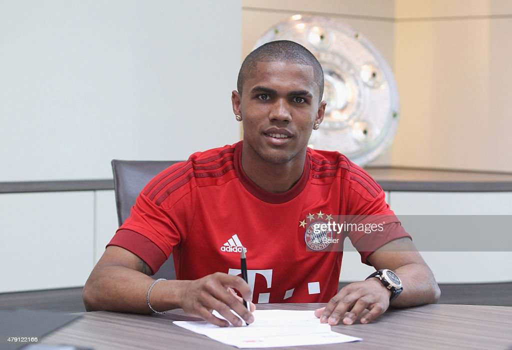 Douglas Costa of Bayern Muenchen signs his new contract at the FC Bayern Muenchen training ground at Saebener Strasse on July 1 2015 in Munich Germany