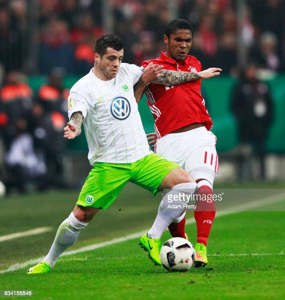 Douglas Costa of Bayern Muenchen tackles Vierinha of VfL Wolfsburg during the DFB Cup Round Of 16 match between Bayern Muenchen and VfL Wolfsburg at...
