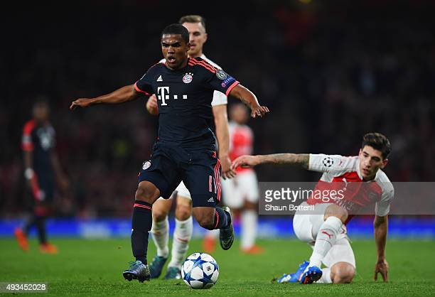 Douglas Costa of Bayern Munich evades Hector Bellerin of Arsenal during the UEFA Champions League Group F match between Arsenal FC and FC Bayern...