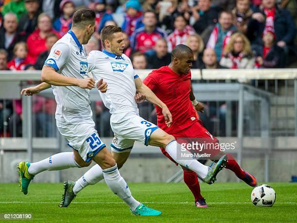 Douglas Costa of Bayern Munich is challenged by Niklas Suele and Pavel Kaderabek of TSG 1899 Hoffenheim during the Bundesliga match between Bayern...