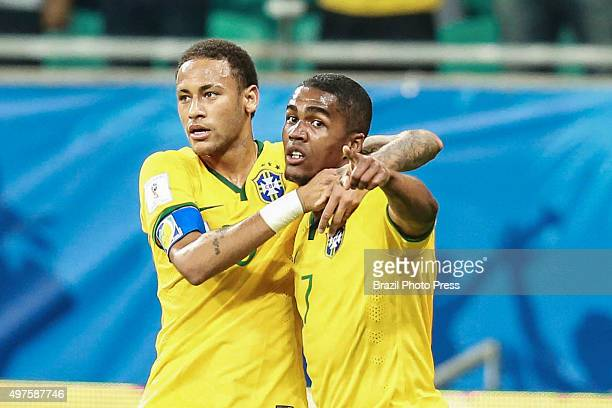 Douglas Costa of Brazil celebrates with Neymar Jr after scoring the first goal of his team during a match between Brazil and Peru as part of FIFA...