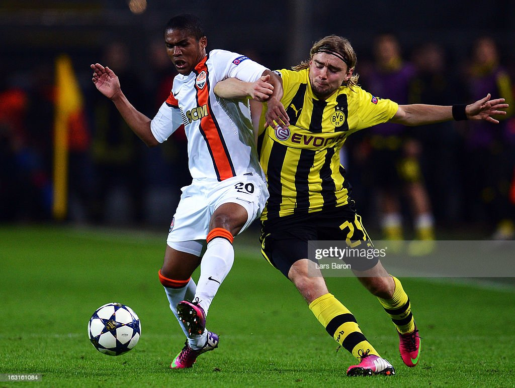 Douglas Costa of Donetsk is challenged by Marcel Schmelzer of Dortmund during the UEFA Champions League round of 16 second leg match between Borussia Dortmund and Shakhtar Donetsk at Signal Iduna Park on March 5, 2013 in Dortmund, Germany.