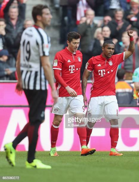 Douglas Costa of FC Bayern Muenchen celebrates his first goal with teammate Robert Lewandowski as David Abraham of Eintracht Frankfurt reacts during...