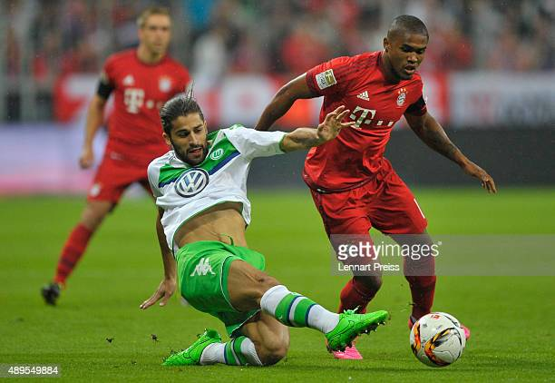 Douglas Costa of FC Bayern Muenchen challenges Ricardo Rodriguez of VfL Wolsburg during the Bundesliga match between FC Bayern Muenchen and VfL...