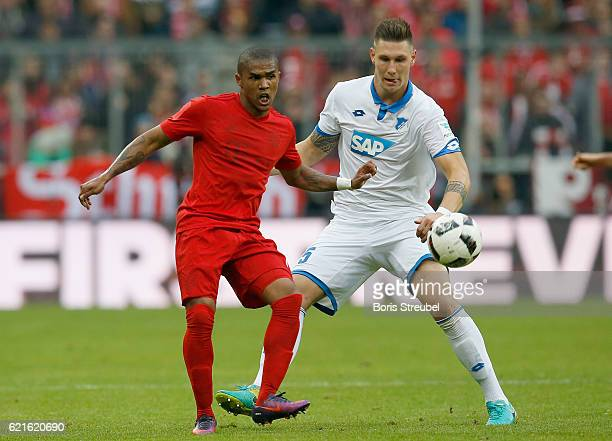 Douglas Costa of FC Bayern Muenchen is challenged by Niklas Suele of TSG Hoffenheim during the Bundesliga match between Bayern Muenchen and TSG 1899...