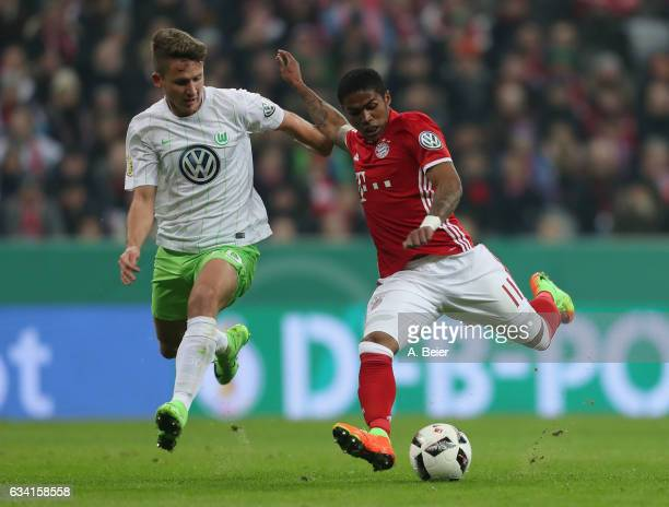 Douglas Costa of FC Bayern Muenchen scores his first goal against Paul Seguin of VfL Wolfsburg during the DFB Cup Round Of 16 match between Bayern...