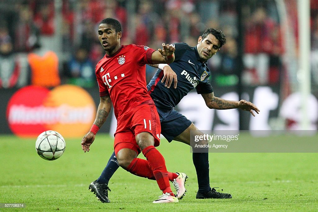 Douglas Costa of FC Bayern Munich and Augusto Fernandez of Atletico Madrid vie for the ball during the Champions League semifinal second leg soccer match between FC Bayern Munich and Atletico Madrid at the Allianz Arena on May 3, 2016, in Munich, Germany.