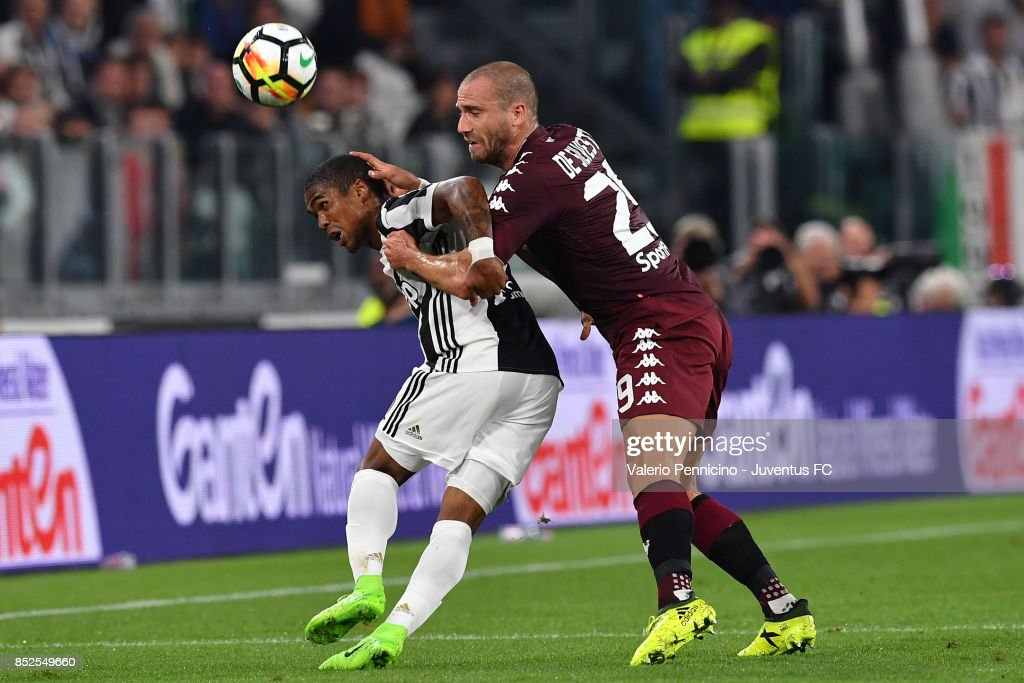 Douglas Costa of Juventus and Lorenzo De Silvestri of Torino in action during the Serie A match between Juventus and Torino FC on September 23, 2017 in Turin, Italy.