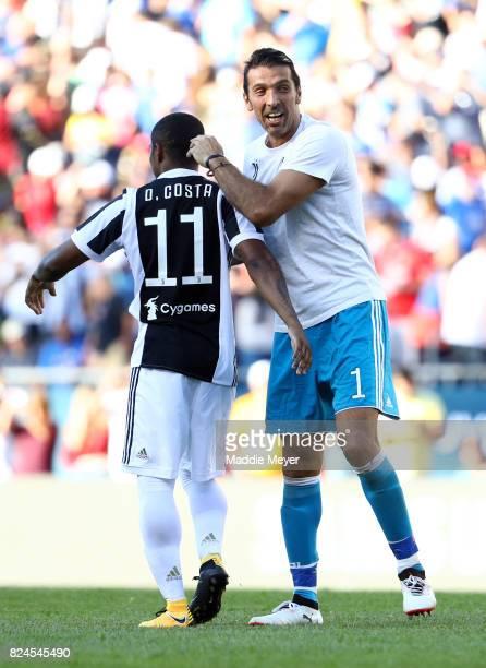 Douglas Costa of Juventus celebrates with Gianluigi Buffon after scoring the game winning goal during penalty kicks to defeat Roma during the...