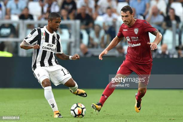 Douglas Costa of Juventus competes for the ball with Artur Ionita of Cagliari during the Serie A match between Juventus and Cagliari Calcio at...