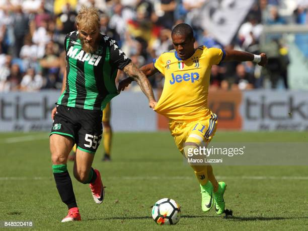 Douglas Costa of Juventus competes for the ball with Timo Letschert of US Sassuolo Calcio during the Serie A match between US Sassuolo and Juventus...