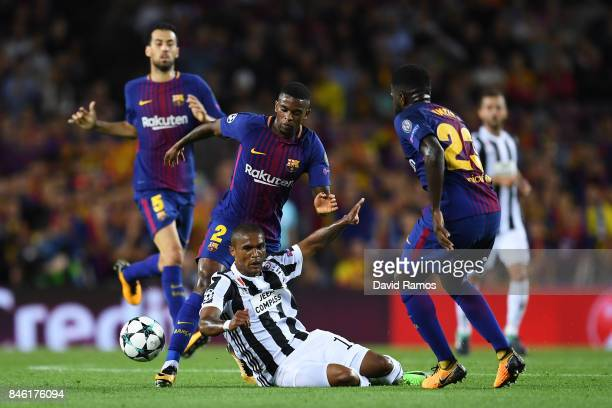 Douglas Costa of Juventus is tackled by Nelson Semedo of Barcelona and Samuel Umtiti of Barcelona during the UEFA Champions League Group D match...