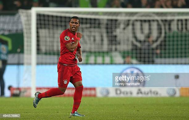 Douglas Costa of Muenchen celebrates after scoring his team's opening goal during the DFB Cup second round match between VfL Wolfsburg and FC Bayern...