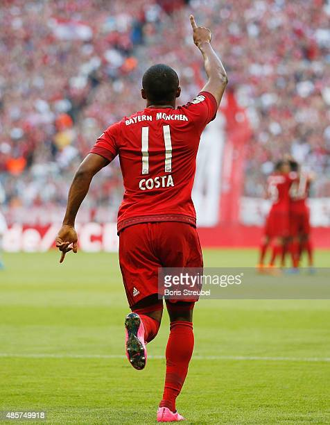 Douglas Costa of Muenchen celebrates after Thomas Mueller scores his team's first goal during the Bundesliga match between FC Bayern Muenchen and...
