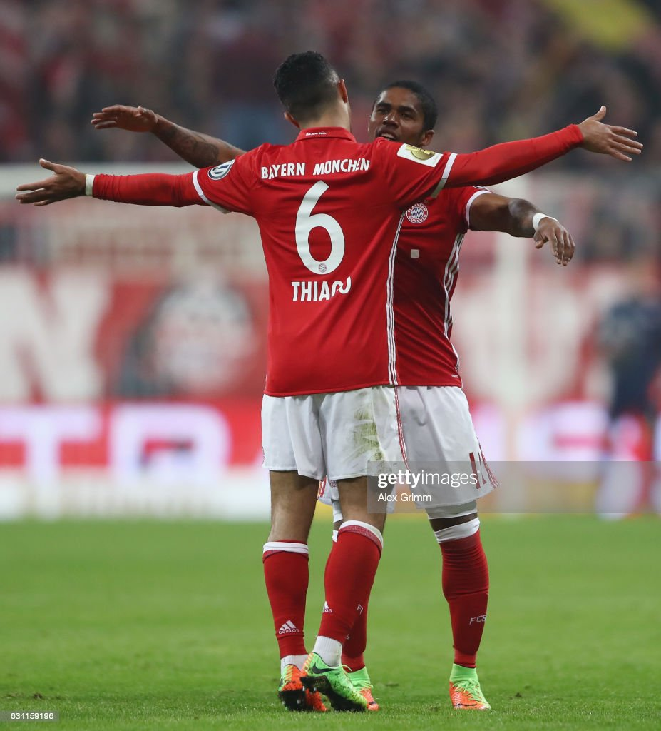 Douglas Costa of Muenchen celebrates his team's first goal with team mate Thiago Alcantara during the DFB Cup Round Of 16 match between Bayern Muenchen and VfL Wolfsburg at Allianz Arena on February 7, 2017 in Munich, Germany.