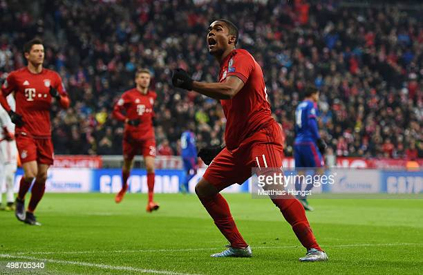 Douglas Costa of Muenchen celebrates with his teammates after scoring his team's first goal during the UEFA Champions League Group F match between FC...