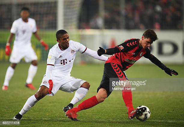 Douglas Costa of Muenchen challenges Pascal Stenzel of Freiburg during the Bundesliga match between SC Freiburg and Bayern Muenchen at...