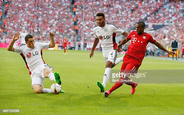 Douglas Costa of Muenchen is challenged by Jonathan Tah and Kyriakos Papadopoulos of Leverkusen during the Bundesliga match between FC Bayern...