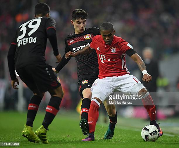 Douglas Costa of Muenchen is challenged by Kai Havertz of Leverkusen during the Bundesliga match between Bayern Muenchen and Bayer 04 Leverkusen at...
