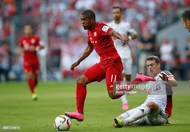 Douglas Costa of Muenchen is challenged by Lars Bender of Leverkusen during the Bundesliga match between FC Bayern Muenchen and Bayer 04 Leverkusen...