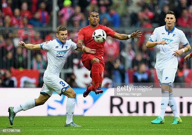 Douglas Costa of Muenchen is challenged by Pavel Kaderabek of Hoffenheim during the Bundesliga match between Bayern Muenchen and TSG 1899 Hoffenheim...