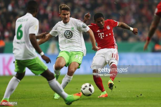 Douglas Costa of Muenchen scores his team's first goal past Paul Seguin and Riechedly Bazoer of Wolfsburg during the DFB Cup Round Of 16 match...