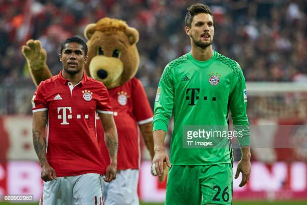 Douglas Costa of Munich and Goalkeeper Sven Ulreich of Munich looks on during the Bundesliga match between Bayern Muenchen and Borussia Dortmund at...