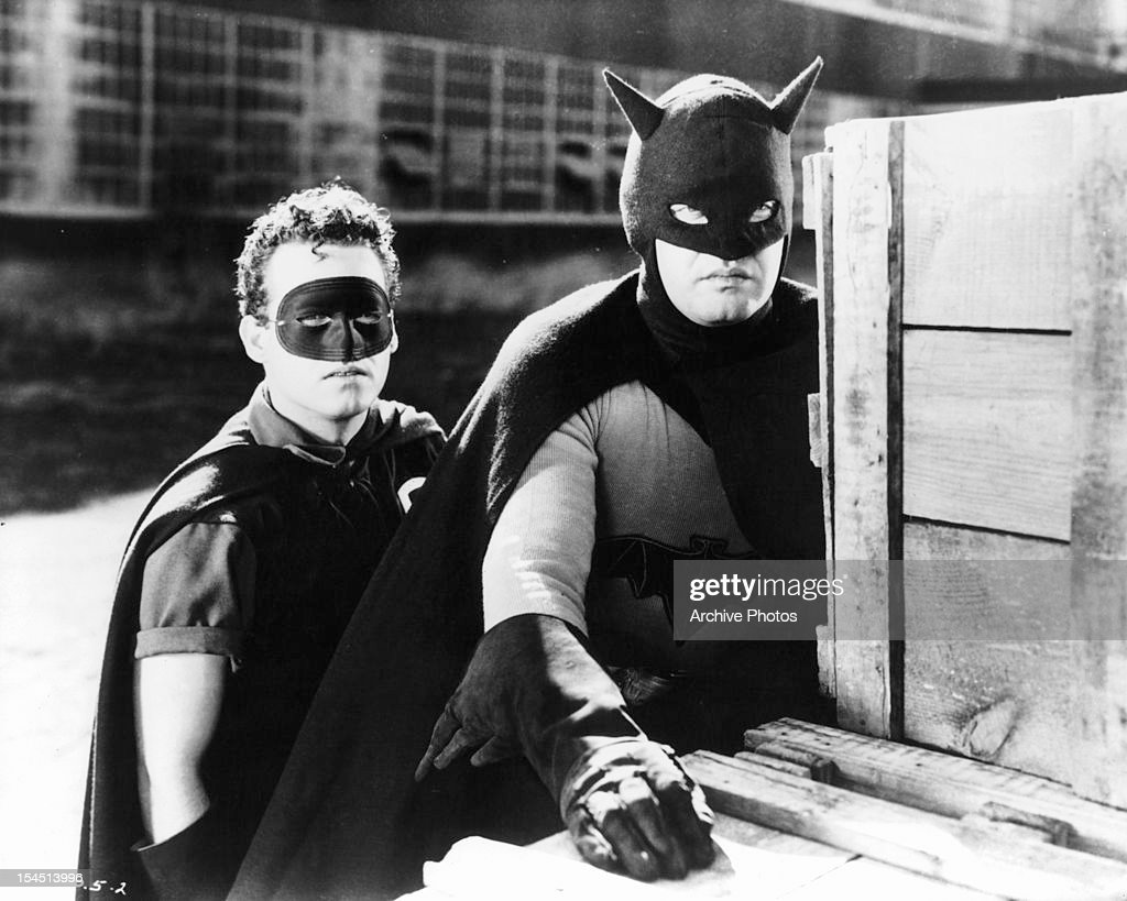 Douglas Croft and Lewis Wilson hide behind crates in a scene from the film 'Batman' 1943
