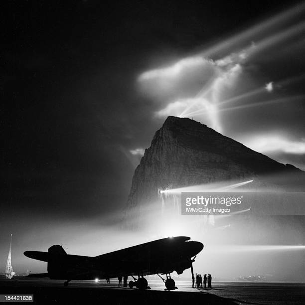 British Overseas Airways Corporation And Qantas 19401945 A Douglas Dakota of BOAC silhouetted by night at Gibraltar by the batteries of searchlights...
