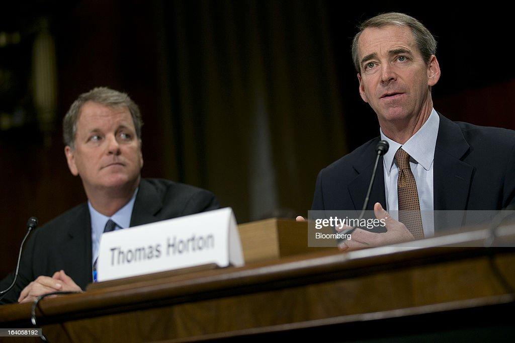 Douglas 'Doug' Parker, chairman and chief executive officer of US Airways Group Inc., left, looks on as Thomas 'Tom' Horton, chairman, president and chief executive officer of AMR Corp.'s American Airlines, speaks during a Senate Judiciary Committee hearing in Washington, D.C., U.S., on Tuesday, March 19, 2013. The proposed merger between American Airlines and US Airways would increase fares, reduce service to smaller communities and make it more difficult for low-cost carriers to compete, two consumer advocates said at a Senate hearing. Photographer: Andrew Harrer/Bloomberg via Getty Images