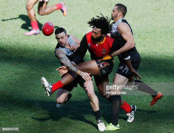 Douglas Gabriel Tuai LAI kicks the ball past Andrew HOWISON of New Zealand during the 2017 AFL International Cup Grand FInal match between New...