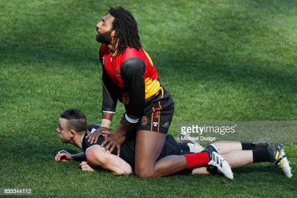 Douglas Gabriel Tuai LAI lays on Andrew HOWISON of New Zealand after kicking the ball during the 2017 AFL International Cup Grand FInal match between...