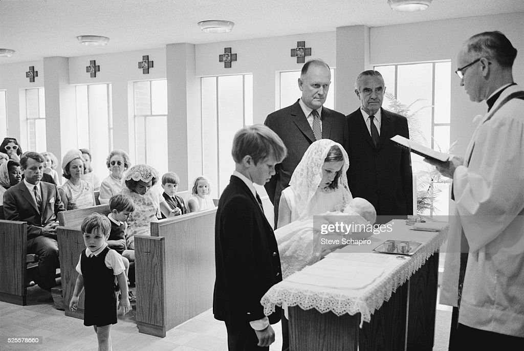 Douglas Kennedy, held by his sister Kerry, is Baptized in Maryland. Standing at the altar is also brother David and Godparents Averill Harriman and Bundy McGeorge. In the pews sits Robert and Ethel Kennedy with the rest of their family.