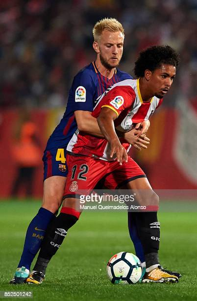 Douglas Luiz of Girona is tackled by Ivan Rakitic of Barcelona during the La Liga match between Girona and Barcelona at Municipal de Montilivi...