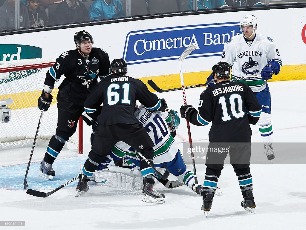 Douglas Murray #3, Justin Braun #61 and Andrew Desjardins #10 of the San Jose Sharks protect the net against Chris Higgins #20 and Jannik Hansen #36 of the Vancouver Canucks during an NHL game on January 27, 2013 at HP Pavilion in San Jose, California.