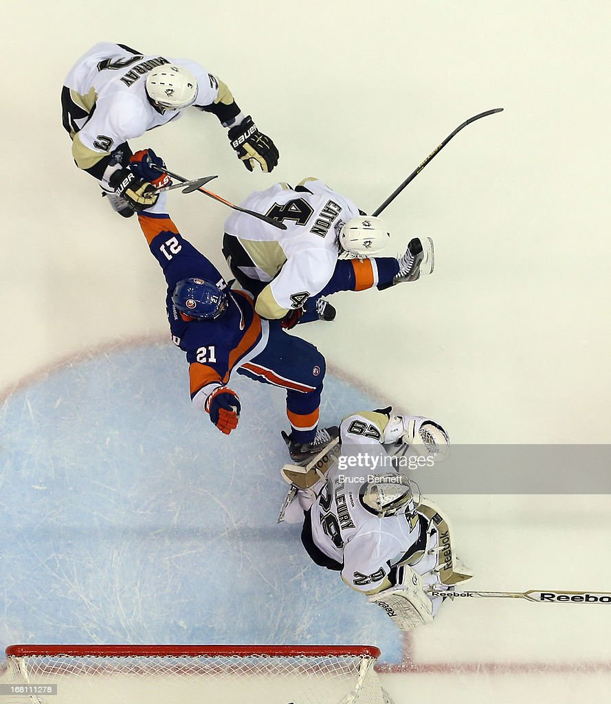 Douglas Murray #3, Mark Eaton #4, and Marc-Andre Fleury #29 of the Pittsburgh Penguins defend against Kyle Okposo #21 of the New York Islanders in Game Three of the Eastern Conference Quarterfinals during the 2013 NHL Stanley Cup Playoffs at the Nassau Veterans Memorial Coliseum on May 5, 2013 in Uniondale, New York. The Penguins defeated the Islanders 5-4 in overtime.