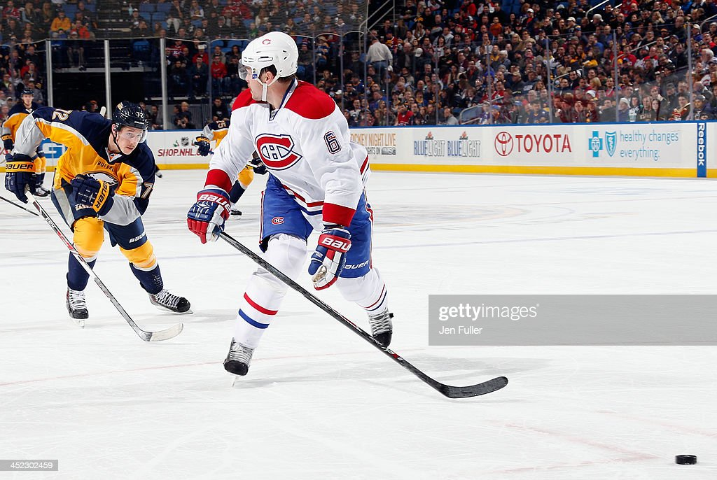 Douglas Murray of the Montreal Canadiens skates for the puck as he looks back at Luke Adam of the Buffalo Sabres at First Niagara Center on November...