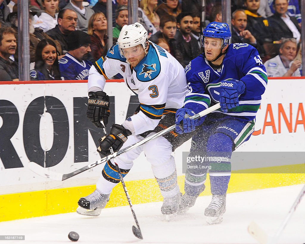 Douglas Murray #3 of the San Jose Sharks battles for the puck against <a gi-track='captionPersonalityLinkClicked' href=/galleries/search?phrase=Jordan+Schroeder&family=editorial&specificpeople=4450940 ng-click='$event.stopPropagation()'>Jordan Schroeder</a> #45 of the Vancouver Canucks during an NHL game at Rogers Arena on March 5, 2013 in Vancouver, British Columbia, Canada.
